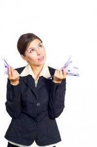 Woman with handfuls of bills and looking confused