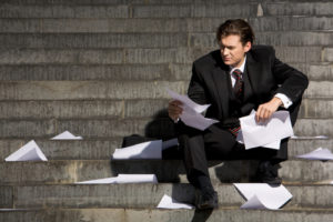Unhappy businessman sitting on stairs